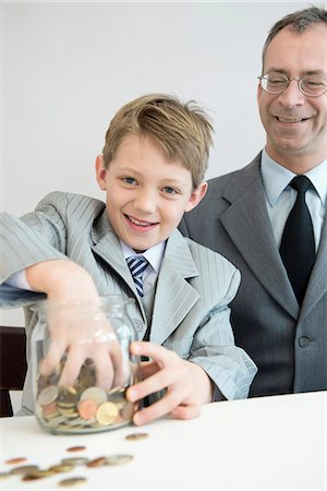 Father and son with piggy bank, smiling Stock Photo - Premium Royalty-Free, Code: 6121-07741403