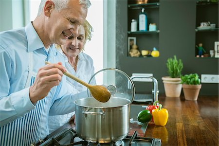 potted plant - Mature couple preparing food in kitchen, smiling Stock Photo - Premium Royalty-Free, Code: 6121-07741400