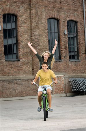 Portrait of teenage couple riding bicycle, smiling Stock Photo - Premium Royalty-Free, Code: 6121-07741545