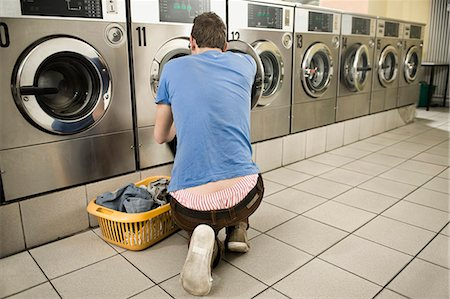 Young man filling up cloths in machine Stock Photo - Premium Royalty-Free, Code: 6121-07741561