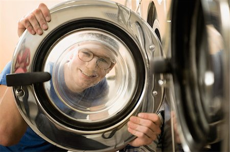 Young man looking through window of washing machine, smiling Stock Photo - Premium Royalty-Free, Code: 6121-07741562
