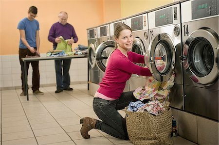 Young woman filling up cloths in washing machine while men in background Stock Photo - Premium Royalty-Free, Code: 6121-07741574