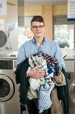 Portrait of young man with laundry, smiling Stock Photo - Premium Royalty-Free, Code: 6121-07741584