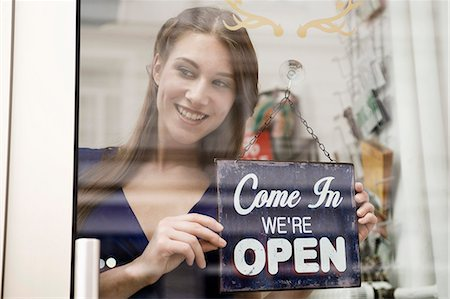 sign - Sales girl holding opening board of fashion shop, smiling Stock Photo - Premium Royalty-Free, Code: 6121-07741503