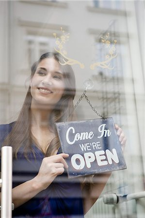 sign - Sales girl holding opening board of fashion shop, smiling Stock Photo - Premium Royalty-Free, Code: 6121-07741504
