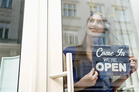 sign - Sales girl holding opening board of fashion shop, smiling Stock Photo - Premium Royalty-Free, Code: 6121-07741505