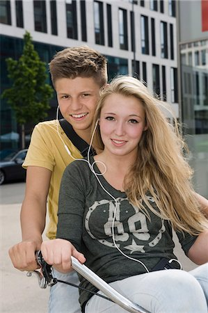 Portrait of teenage couple listening music on bicycle, smiling Stock Photo - Premium Royalty-Free, Code: 6121-07741513