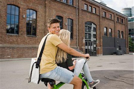 Teenage couple sitting on bicycle, smiling Stock Photo - Premium Royalty-Free, Code: 6121-07741512