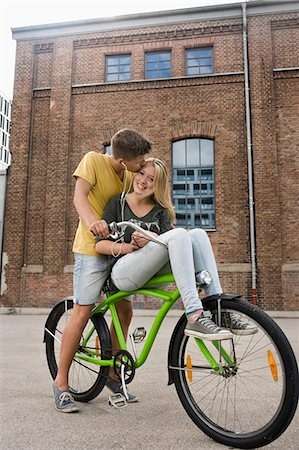 Teenage boy kissing teenage girl, smiling Stock Photo - Premium Royalty-Free, Code: 6121-07741523