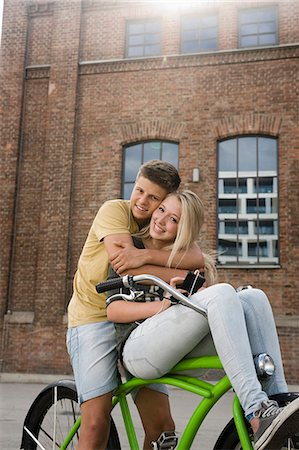 Portrait of teenage couple embracing on bicycle, smiling Stock Photo - Premium Royalty-Free, Code: 6121-07741522