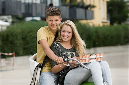 Portrait of teenage couple listening music on bicycle, smiling Stock Photo - Premium Royalty-Free, Code: 6121-07741525