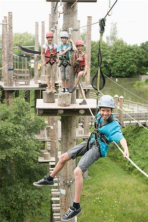 Boys and girls climbing crag, smiling Stock Photo - Premium Royalty-Free, Code: 6121-07741668