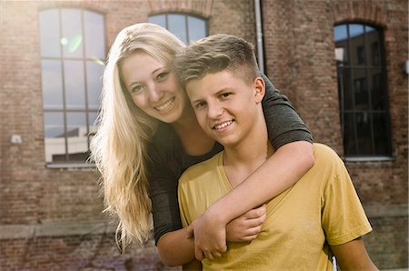 Portrait of teenage couple embracing each other, smiling Stock Photo - Premium Royalty-Free, Code: 6121-07741604