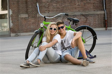 Teenage couple sitting on street with bicycle, smiling Stock Photo - Premium Royalty-Free, Code: 6121-07741606