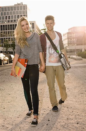 Portrait of teenage couple coming from school, smiling Stock Photo - Premium Royalty-Free, Code: 6121-07741613