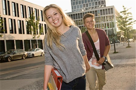 Portrait of teenage couple coming from school, smiling Stock Photo - Premium Royalty-Free, Code: 6121-07741614