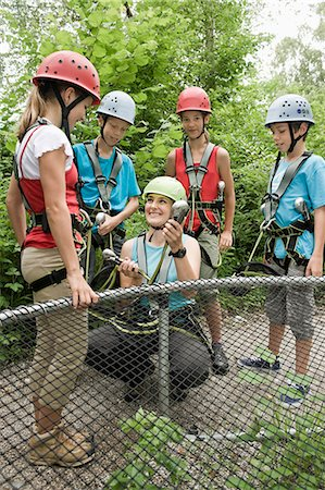 Young woman giving instruction to childrens for climbing crag Stock Photo - Premium Royalty-Free, Code: 6121-07741619