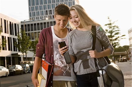 Teenage couple listening music with smart phone, smiling Stock Photo - Premium Royalty-Free, Code: 6121-07741620