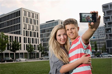 Portrait of teenage couple taking picture with smart phone, smiling Stock Photo - Premium Royalty-Free, Code: 6121-07741633
