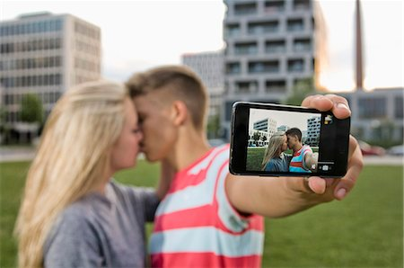 Teenage couple taking self portrait with themselves Stock Photo - Premium Royalty-Free, Code: 6121-07741631