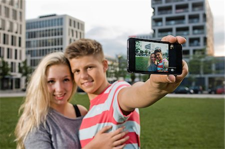 Portrait of teenage couple taking picture with smart phone, smiling Stock Photo - Premium Royalty-Free, Code: 6121-07741632