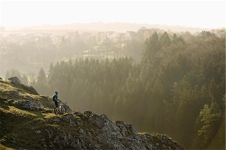 Young man mountainbiking at sunrise, Bavaria, Germany Stock Photo - Premium Royalty-Free, Code: 6121-07741743