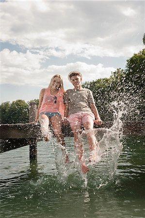 Teenage couple sitting on a jetty splashing water Stock Photo - Premium Royalty-Free, Code: 6121-07741747