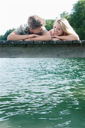 Teenage couple lying side by side on a jetty at lake Stock Photo - Premium Royalty-Free, Code: 6121-07741749