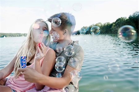 Teenage couple blowing soap bubbles on a jetty at lake Stock Photo - Premium Royalty-Free, Code: 6121-07741789