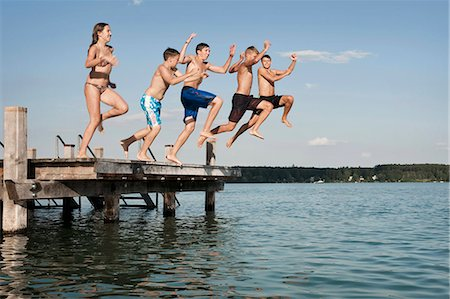 Five teenagers jumping from a jetty into lake Stock Photo - Premium Royalty-Free, Code: 6121-07741790