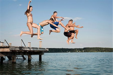 Five teenagers jumping from a jetty into lake Stock Photo - Premium Royalty-Free, Code: 6121-07741791