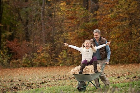 person - Father pushing happy daughter in wheelbarrow Stock Photo - Premium Royalty-Free, Code: 6121-07741716