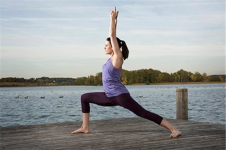 Woman practicing yoga on jetty, Woerthsee, Bavaria, Germany Stock Photo - Premium Royalty-Free, Code: 6121-07741868