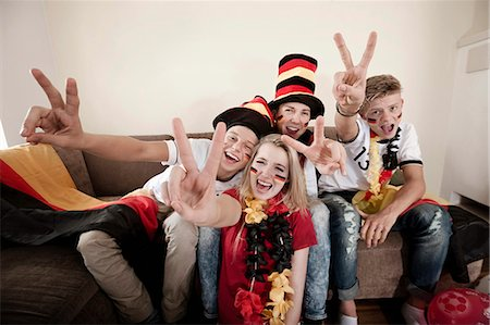 Teenage soccer fans posing in living room Stock Photo - Premium Royalty-Free, Code: 6121-07741922
