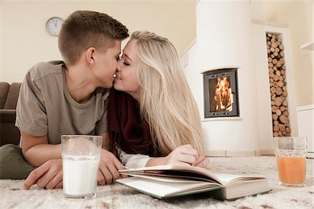 Teenage couple in love cuddling on carpet in front of fireside Stock Photo - Premium Royalty-Free, Code: 6121-07741932