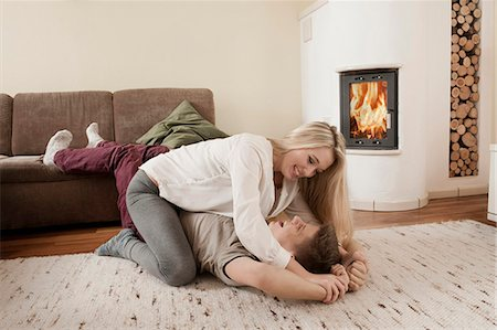Teenage couple playfighting on carpet in front of fireside Stock Photo - Premium Royalty-Free, Code: 6121-07741934