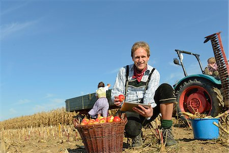 family apple orchard - Mature man checking digital tablet in front of basket with apples, woman and son in background, Bavaria, Germany Stock Photo - Premium Royalty-Free, Code: 6121-07739948