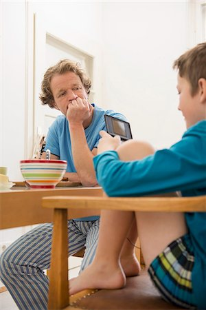 sad child sitting - Father looking at son playing video game at breakfast table Stock Photo - Premium Royalty-Free, Code: 6121-07809658