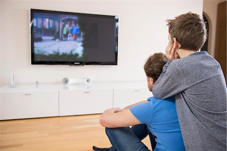 Father and son watching TV at home Stock Photo - Premium Royalty-Free, Code: 6121-07809661