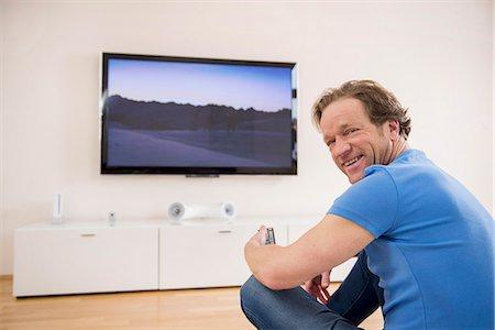 Man watching TV at home Stock Photo - Premium Royalty-Free, Code: 6121-07809669