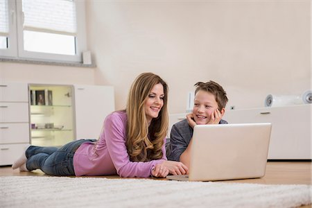 floor - Mother and son lying on floor looking at laptop Stock Photo - Premium Royalty-Free, Code: 6121-07809672