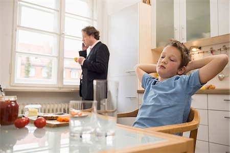 Bored boy in kitchen with father on the phone in background Stock Photo - Premium Royalty-Free, Code: 6121-07809694