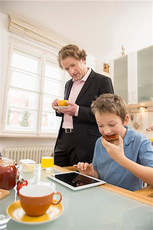 funny looking people - Boy using digital tablet during breakfast with father watching Stock Photo - Premium Royalty-Free, Code: 6121-07809698