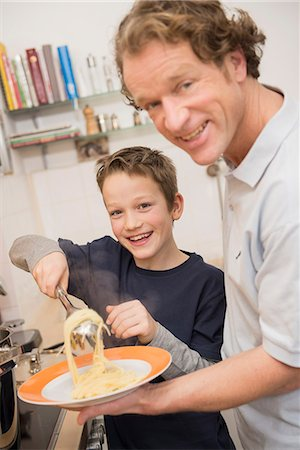 Father and son eating spaghetti in kitchen Stock Photo - Premium Royalty-Free, Code: 6121-07809791