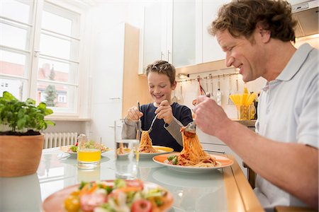 family table eating together - Father and son eating spaghetti and salad in kitchen Stock Photo - Premium Royalty-Free, Code: 6121-07809798