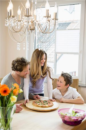 family table eating together - Family eating pizza and salad at home Stock Photo - Premium Royalty-Free, Code: 6121-07809847