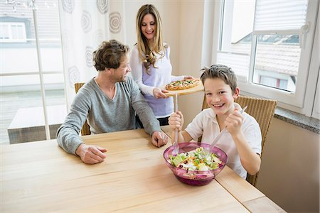 family table eating together - Family eating pizza and salad at home Stock Photo - Premium Royalty-Free, Code: 6121-07809845