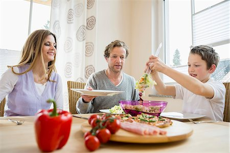 elementary age - Family eating pizza and salad at home Stock Photo - Premium Royalty-Free, Code: 6121-07809848