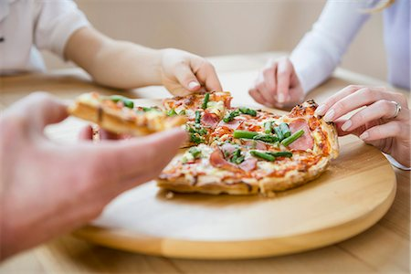Family sharing a pizza Stock Photo - Premium Royalty-Free, Code: 6121-07809849