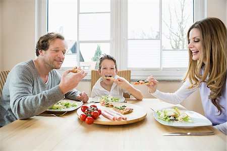 family table eating together - Family eating pizza and salad at home Stock Photo - Premium Royalty-Free, Code: 6121-07809850
